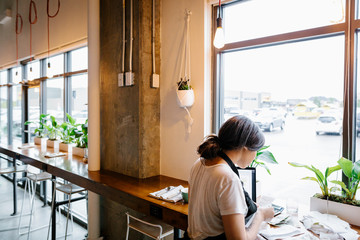 Female cafe owner working at window