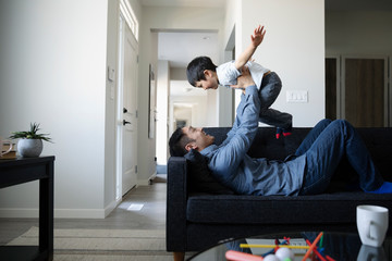 Playful father and son on living room sofa
