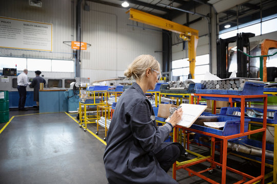 Female machinist with clipboard in factory