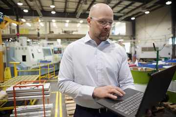 Machine shop supervisor using laptop in factory