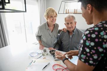 Home healthcare nurse helping senior couple with medical marijuana