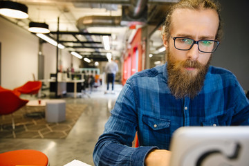 Focused businessman working at laptop in coworking space