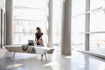 Businesswoman working at laptop in office lobby
