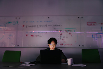 Focused male computer programmer working late at laptop in office