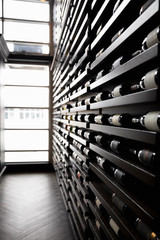 Wine bottles in a row on racks in wine bar