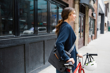 Businesswoman with bicycle on urban sidewalk Fotomurales