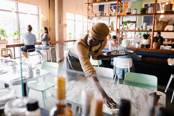 Male worker cleaning table in cafe