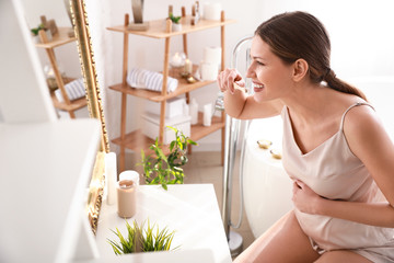 Fotomurales - Young pregnant woman brushing teeth in bathroom