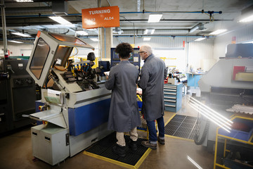 Machinists operating machinery in factory