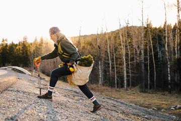 Female volunteer planting trees in woods