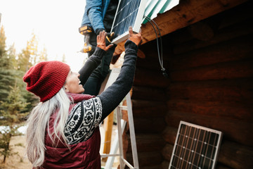 Happy woman installing solar panels on cabin