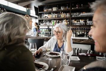 Happy senior women friends dining in restaurant