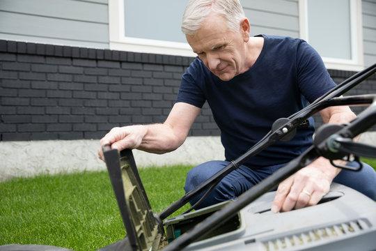 Senior man fixing lawn mower in yard