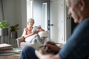 Senior woman reading book in living room armchair