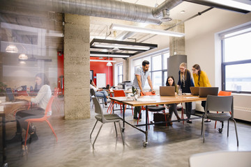 Business people meeting at laptop in open plan office