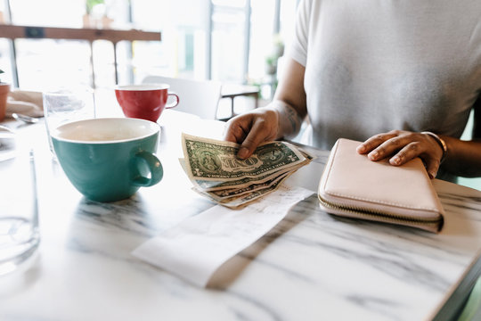 Woman leaving cash at cafe table