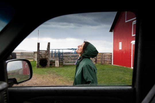 Serene female farmer standing outside truck on farm
