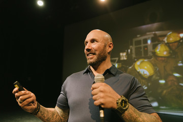 Male firefighter with tattoos giving inspirational speech on stage