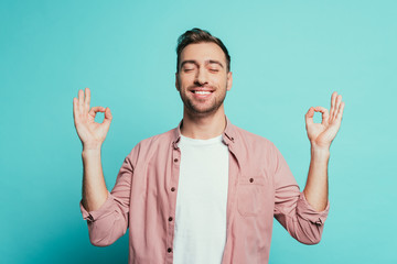 cheerful man with closed eyes showing om gesture, isolated on blue Fotobehang