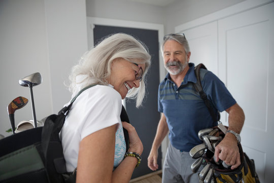 Happy senior couple with golf bags leaving home