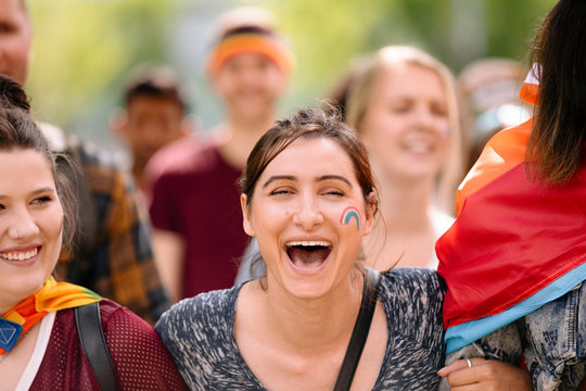 Student with rainbow on face cheering at gay pride parade