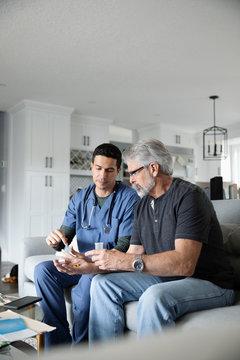 Home healthcare nurse explaining prescription medication to senior man in living room