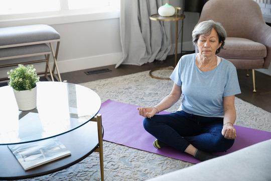 Serene senior woman meditating on yoga mat in living room