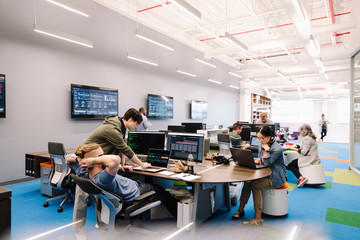 Computer programmers working in open plan office