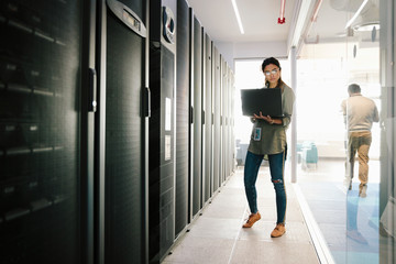 Female IT technician with laptop working in network server room