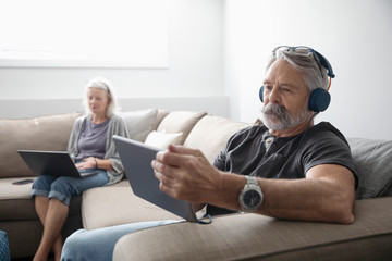 Senior couple with laptop and digital tablet on living room sofa