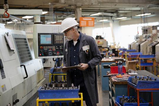 Machine shop supervisor examining equipment on factory floor