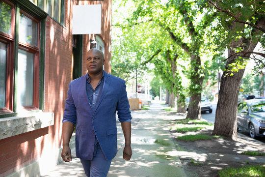 Businessman walking on urban sidewalk