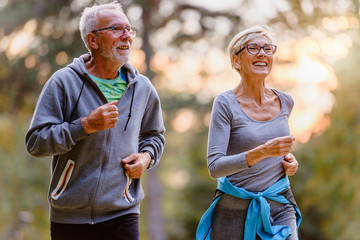 Foto op Plexiglas Jogging Cheerful active senior couple jogging in the park. Exercise together to stop aging.