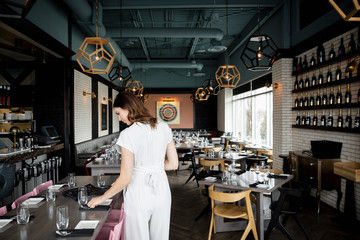 Female hostess preparing tables in empty restaurant