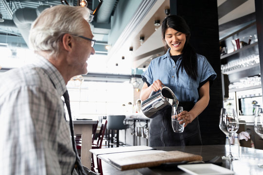 Friendly waitress pouring water for senior man dining in restaurant
