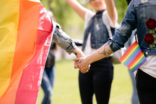 Couple holding hands at gay pride festival with rainbow flag