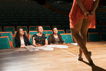 Female judges watching dancer on stage in auditorium