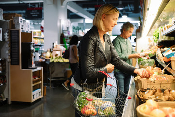 Woman shopping for apples in grocery store