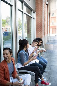 Friends eating burritos on urban sidewalk