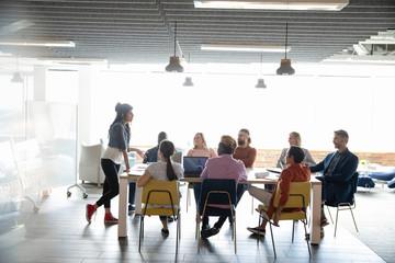 Businesswoman leading meeting in open plan office