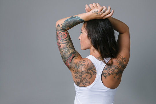 Rear view portrait young woman with tattoos wearing racerback tank top
