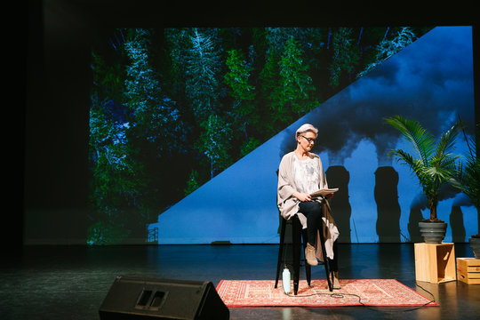 Female inspirational climate change speaker with notebook practicing on stage
