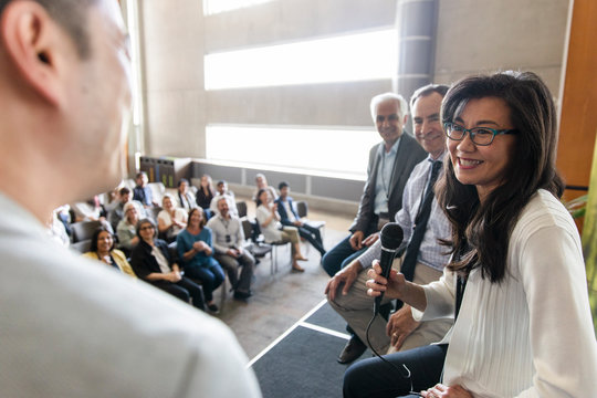 Smiling businesswoman with microphone speaking on stage at conference