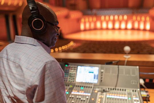 Male sound engineer at sound board in auditorium