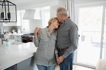 Affectionate senior couple hugging and kissing in kitchen