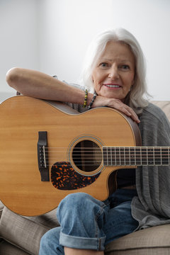 Portrait smiling senior woman playing guitar