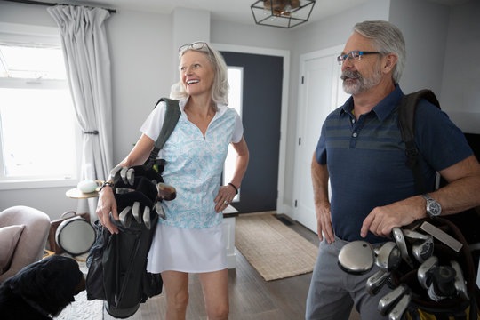 Senior couple with golf bags in living room