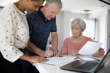 Financial advisor watching senior man signing contract