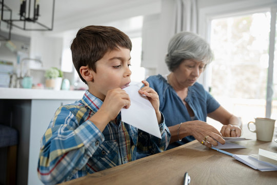 Grandmother and grandson sealing envelopes at dining table