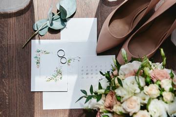 Luxury set of wedding invitations, wedding rings, elegant bride shoes on high heels on wood brown...